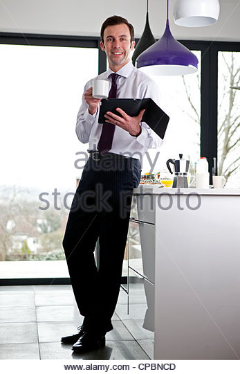 A businessman standing in a kitchen holding a coffee cup digital tablet - Stock-Bilder