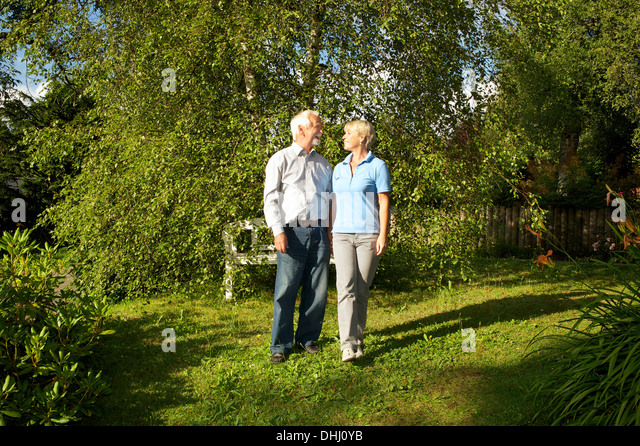 Portrait of senior couple in garden - Stock Image
