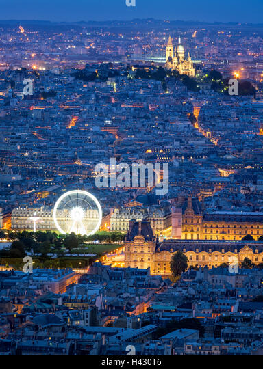 Aerial view of Paris rooftops at dusk, including The Louvre, and Sacre Coeur in Montmartre. Blue hour in the City - Stock Image