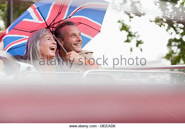Happy couple with British flag umbrella riding double decker bus - Stock Image