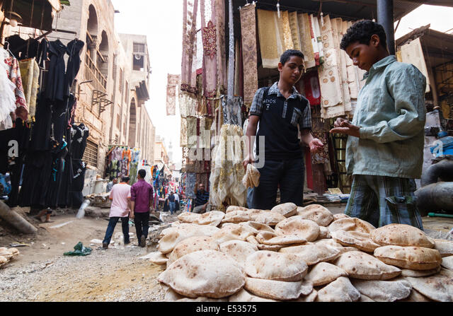 Bazaar street scene with child selling bread. Islamic Cairo, Egypt - Stock Image