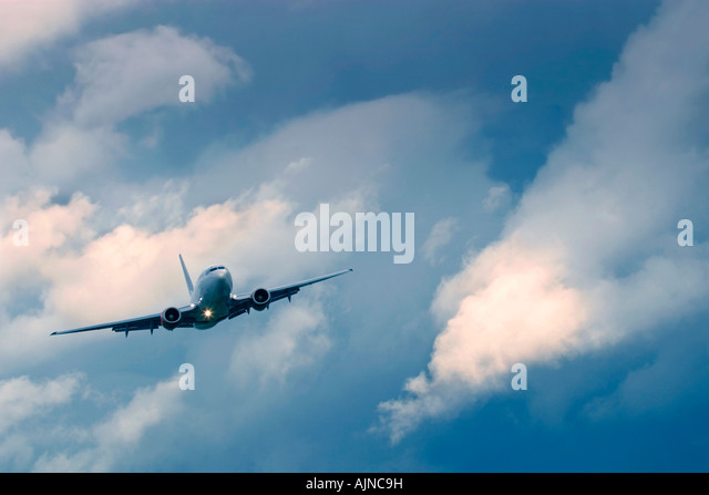 Commercial airplane during flight in the dramatic stormy clouds - Stock Image