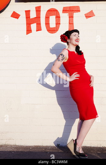 retro style woman in front of a 'hot' wall laughing - Stock Image