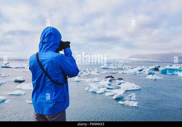 nature travel photographer, person taking photo of arctic icebergs in Iceland - Stock-Bilder
