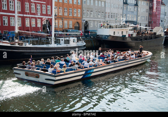 A canal cruise boat taking passengers on a tour of Copenhagen and its surrounding areas in Nyhavn Harbour, Copenhagen, - Stock Image
