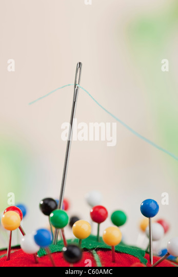 USA, Illinois, Metamora, studio shot of needle and blue thread in pin cushion - Stock Image