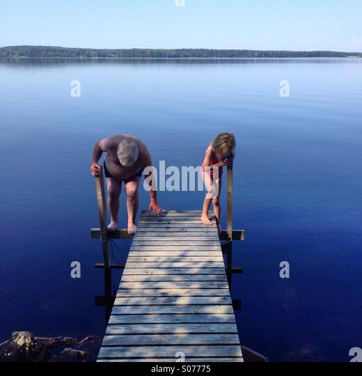 Grandfather and granddaughter go swimming in a Nordic lake together - Stock-Bilder