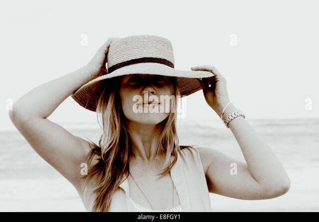 Portrait of a woman standing on beach holding her hat - Stock Image