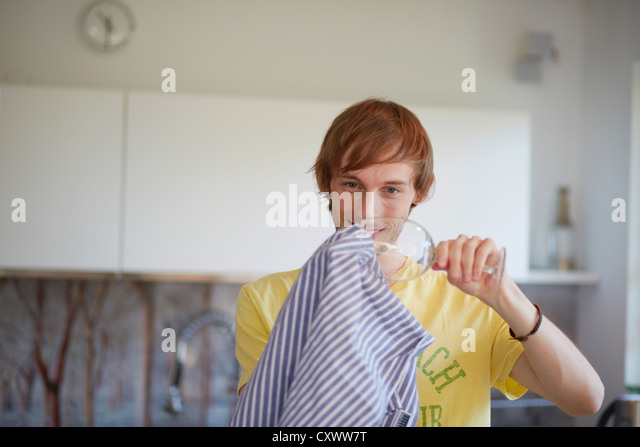 Man polishing wine glass in kitchen - Stock Image