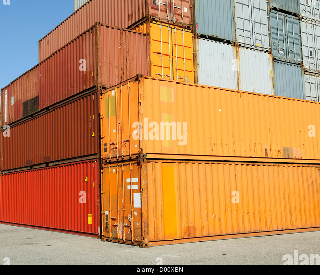 Cargo shipping containers stacked at harbor freight terminal under clear blue sky - Stock Image
