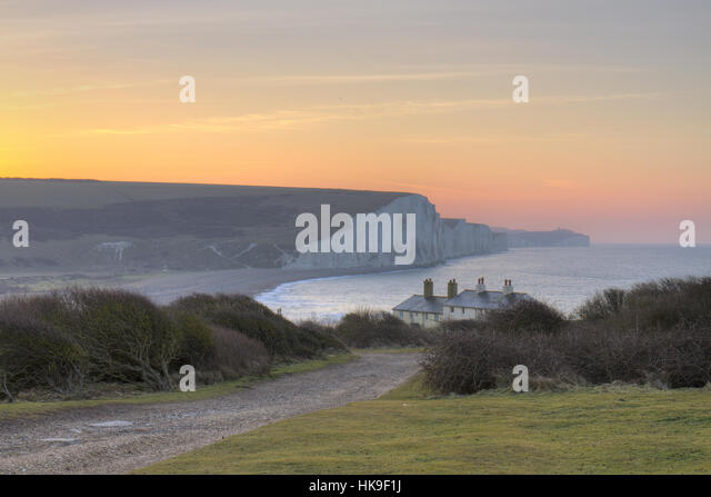 The Seven Sisters cliffs and coastguard cottages at dawn. From Seaford Head, South Downs, East Sussex, England. - Stock-Bilder