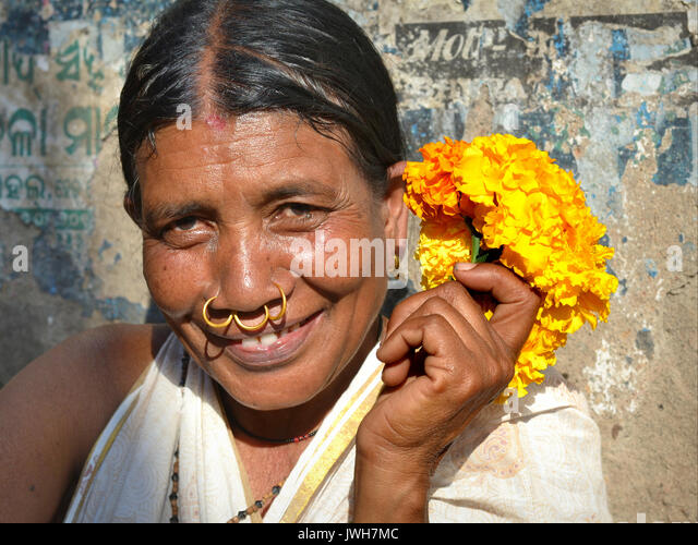 Closeup street portrait (outdoor headshot, seven-eighths view) of a smiling mature Indian Adivasi flower seller - Stock Image