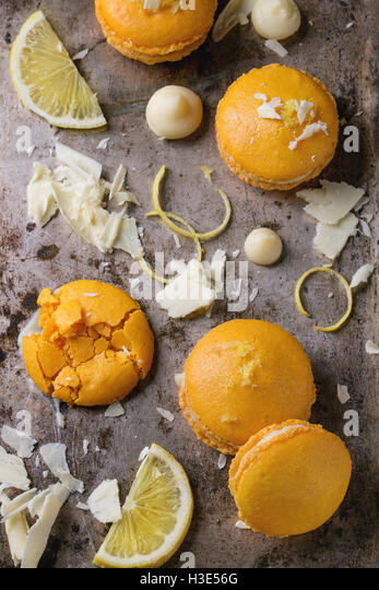 Whole and broken orange lemon homemade macaroons with chopped white chocolate and citrus sugar and zest over old - Stock Image