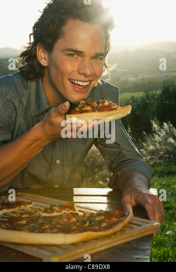 Italy, Tuscany, Young man eating pizza at dusk - Stock Image