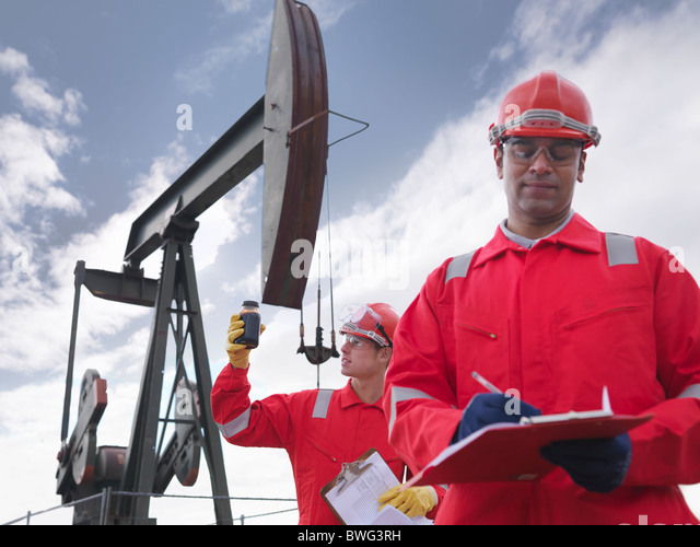 Workers with crude oil and oil well - Stock-Bilder
