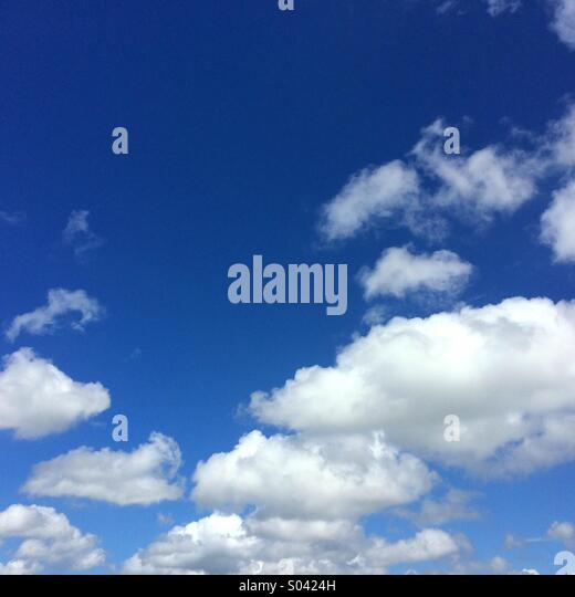 Blue sky and fluffy white clouds can be used for background with space for text - Stock Image