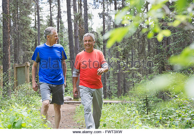 Middle-aged men walking in forest - Stock Image