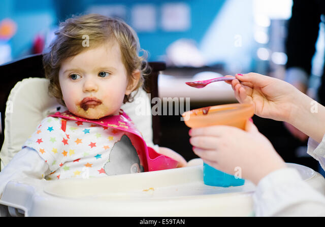 Girl feeding baby girl in high chair - Stock Image