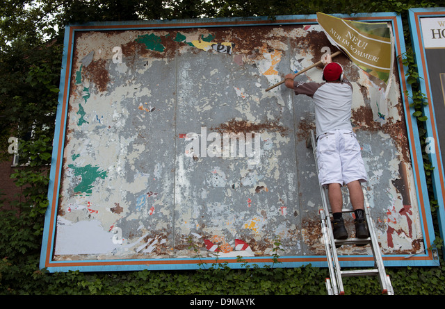 Worker cleaning away old billboard advertising - Stock Image