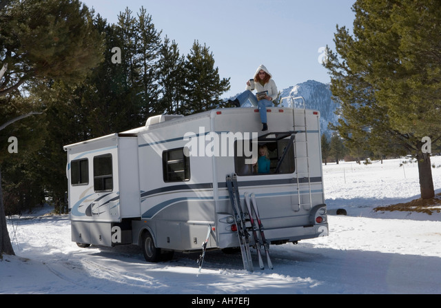 Mature woman sitting on top of a recreational vehicle with her two daughters inside it - Stock Image