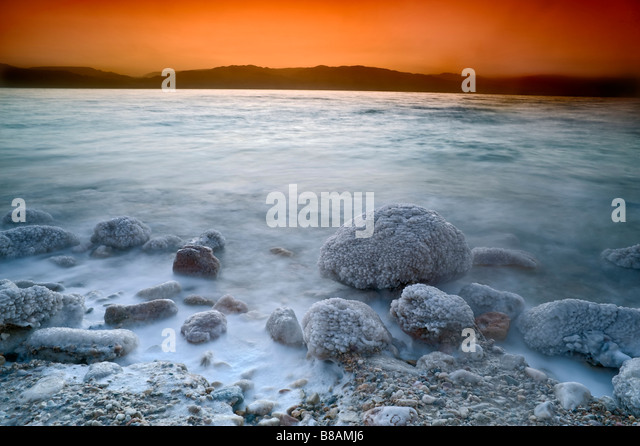 sunrise over the dead sea with waves in motion blur - Stock Image