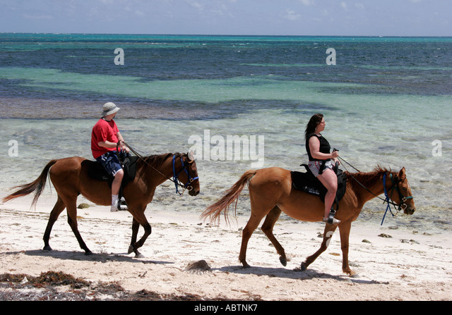 Grand Turk Atlantic Ocean Indigenous Horse Shelter horseback riding couple beach - Stock Image
