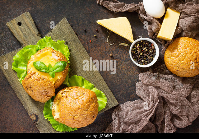 Delicious baked burger from bacon, eggs, cheese served with fresh lettuce leaves. Ingredients for cooking scrambled - Stock Image