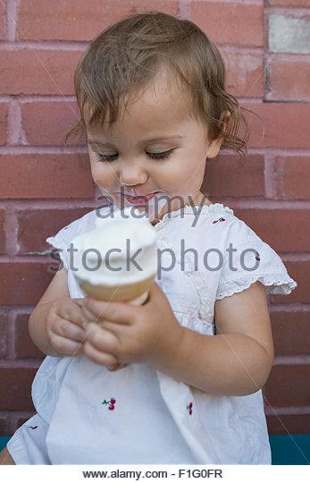 Baby girl enjoying soft serve ice cream cone - Stock Image