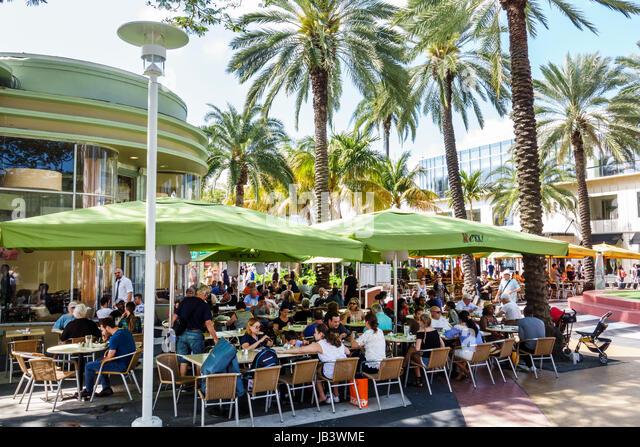 Miami Beach Florida Lincoln Road pedestrian mall Nexxt Cafe restaurant outdoor dining al fresco umbrellas crowded - Stock Image