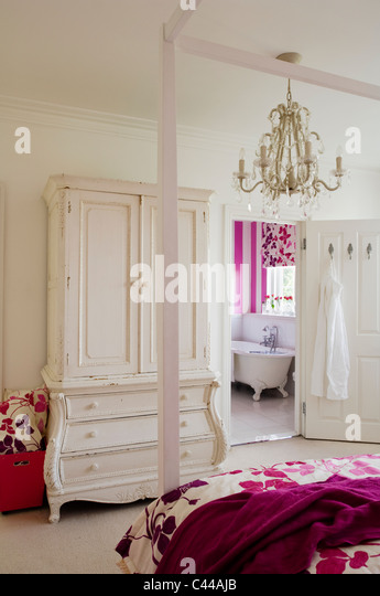 Fourposter bed in bedroom with white wardrobe with drawers, chandelier and en suite - Stock Image