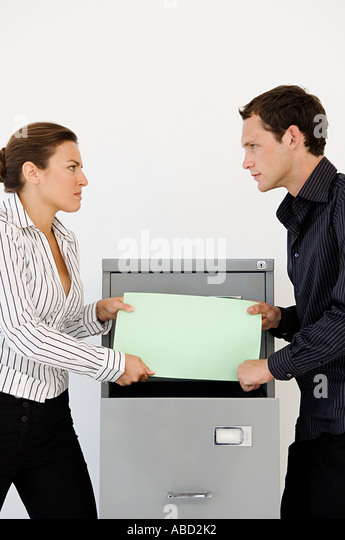 Businessman and businesswoman fighting over file - Stock Image