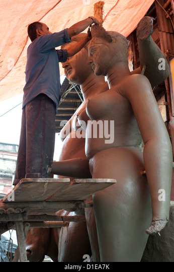 Sculptor working on large moulded clay deity from the River Hugli, Kumartuli district, Kolkata, West Bengal, India, - Stock Image