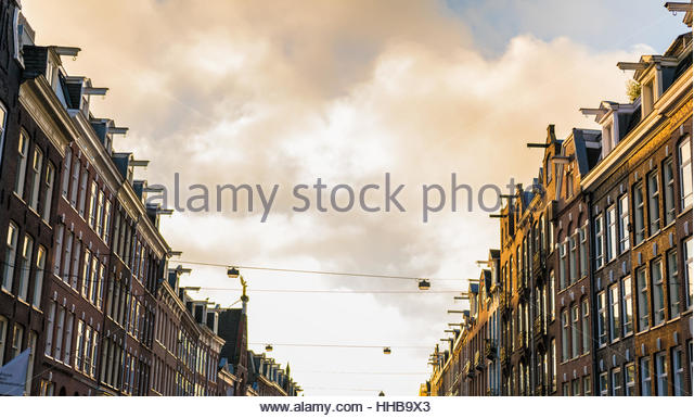 Big Amsterdam street with rows of houses on each side - Stock Image