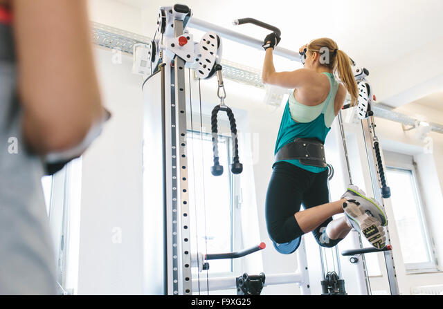 Woman doing pull-ups with weights in gym - Stock Image