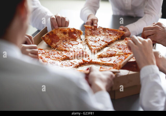 Business team eating pizza in office sitting around the table - Stock Image