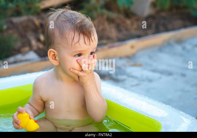 child bathes in inflatable pool outdoors, close-up portrait - Stock-Bilder