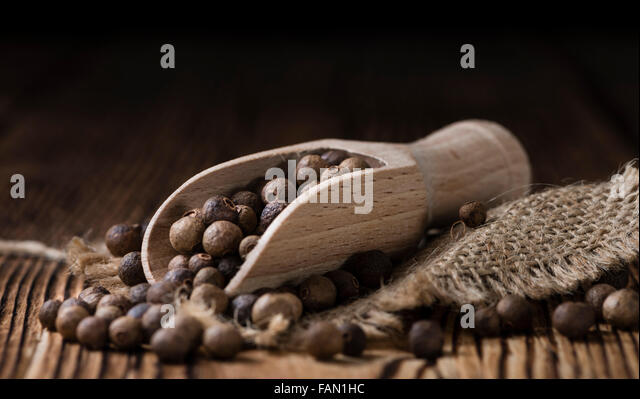 Portion of Allspice (detailed close-up shot) on wooden background - Stock Image