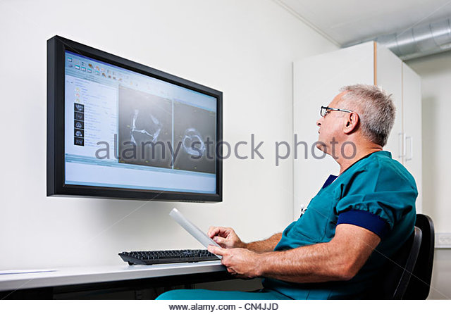 Doctor looking at scans on monitor - Stock Image