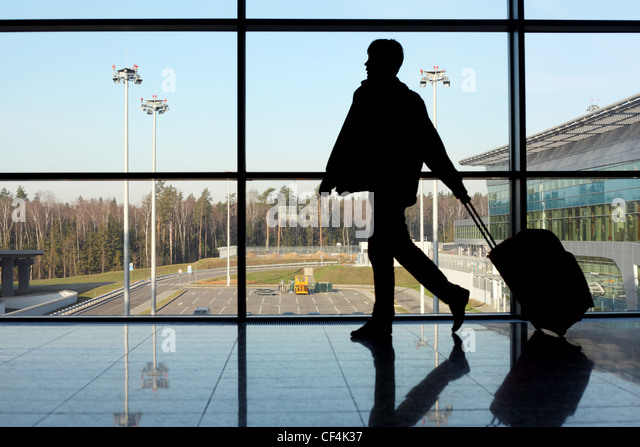 silhouette of man with luggage walking left near window in airport focus on street - Stock Image