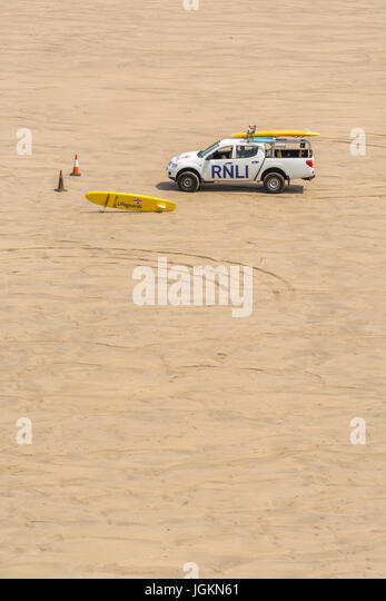 RNLI lifeguard vehicle on Fistral beach (Newquay) during Summer holiday season. - Stock Image