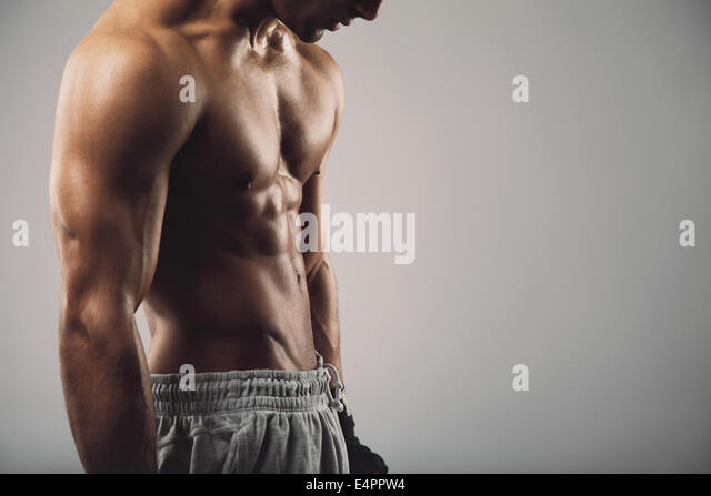 Cropped image of masculine young guy on grey background with copy space.  Workout and fitness theme. - Stock Image