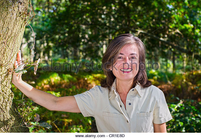 Smiling older woman standing in forest - Stock Image