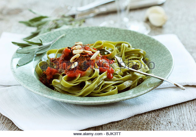 Spinach pasta with fried sage leaves in tomato sauce - Stock Image