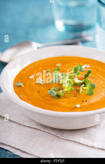 Curried carrot soup with cream and fresh herbs - Stock Image
