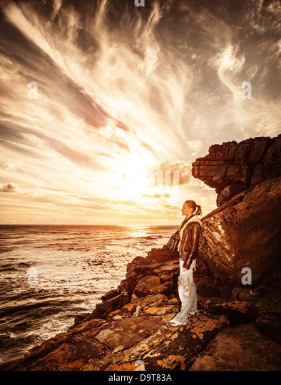 Traveler girl on the cliff, beautiful sunset on seascape, photographer woman, active lifestyle, expedition to mountains - Stock Image