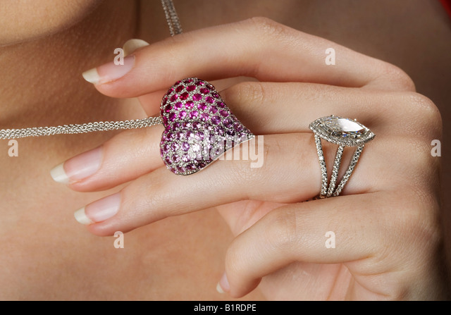 A woman holding a gem studded heart shaped necklace while wearing a brilliant diamond ring. - Stock Image