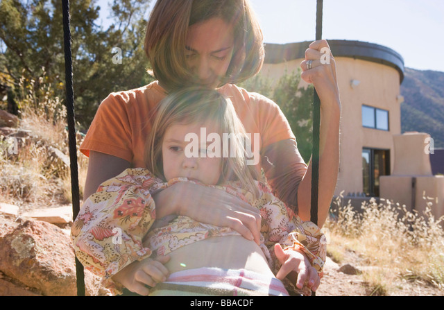 A mother and daughter on a swing together - Stock-Bilder