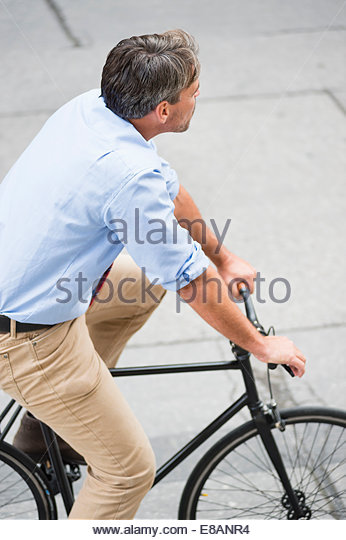 High angle view of mature businessman cycling on sidewalk - Stock Image