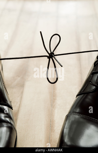 Shoelaces tied together - Stock Image