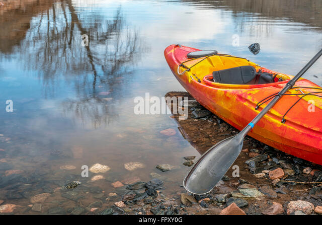 colorful river kayak with a paddle on rocky lake shore with a tree reflection - recreation concept - Stock-Bilder
